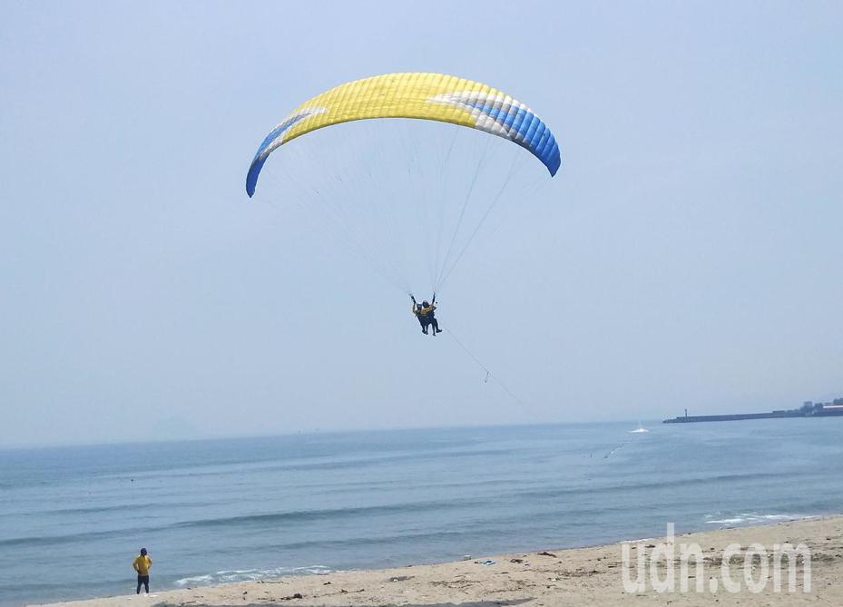 有業者在翡翠灣沙灘首創「水上飛行傘」,不同於從山坡高空跳下,飛行傘是在沙灘上,透過水上摩托車拖曳飛上天空,再放開翱翔。記者游明煌/攝影