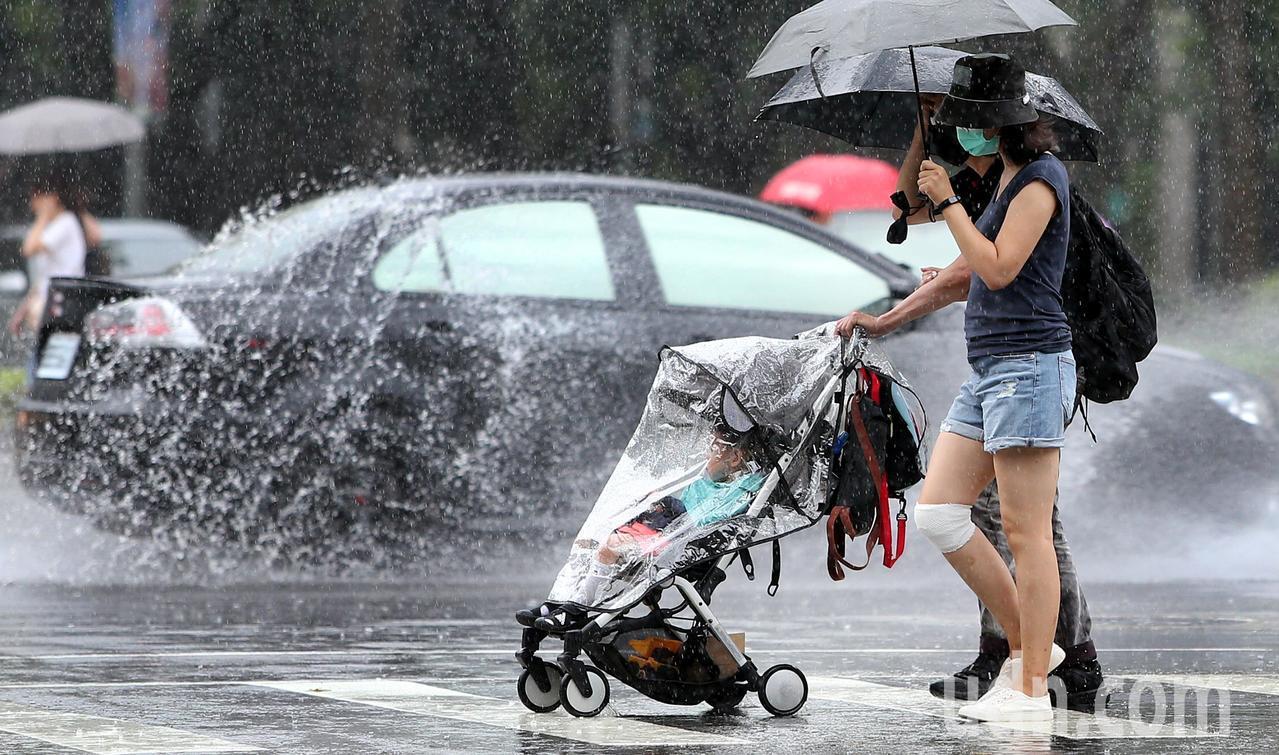 梅雨鋒面影響,台北大小雨勢不斷,一對夫妻推著嬰兒車穿越濕漉漉的馬路,一旁轎車駛過...