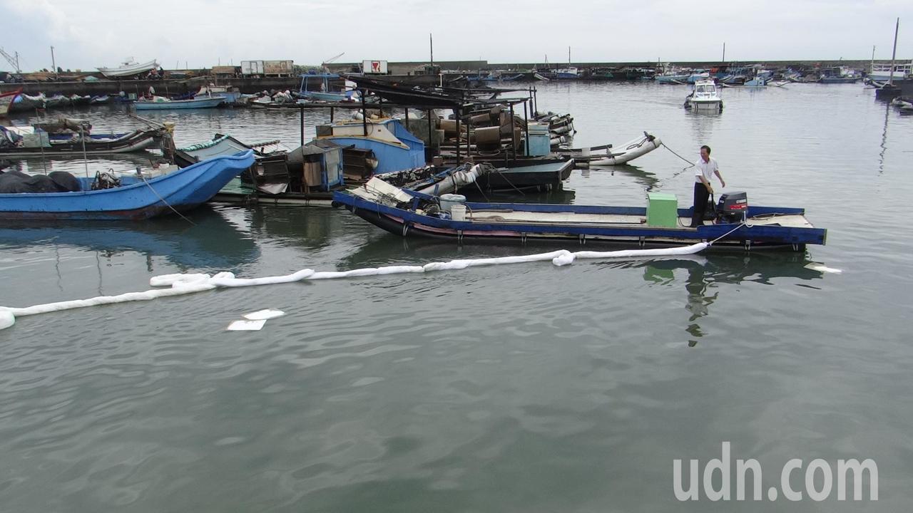 環保局在漁港出口架設一層層攔油繩,以防油漬流出外海。記者蔡維斌/攝影