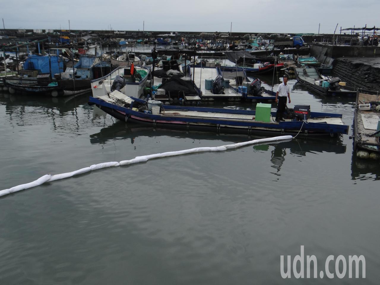 環保局在漁港出口架設攔油繩,以防油漬流出外海。記者蔡維斌/攝影