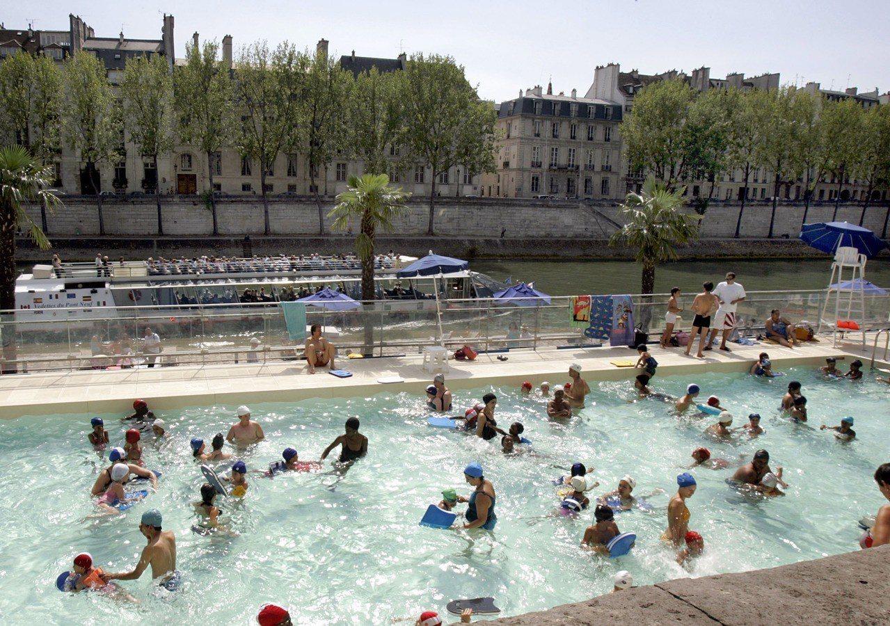法國近日遭遇攝氏40度的熱浪襲擊,巴黎部分游泳池夜間開放。美聯社