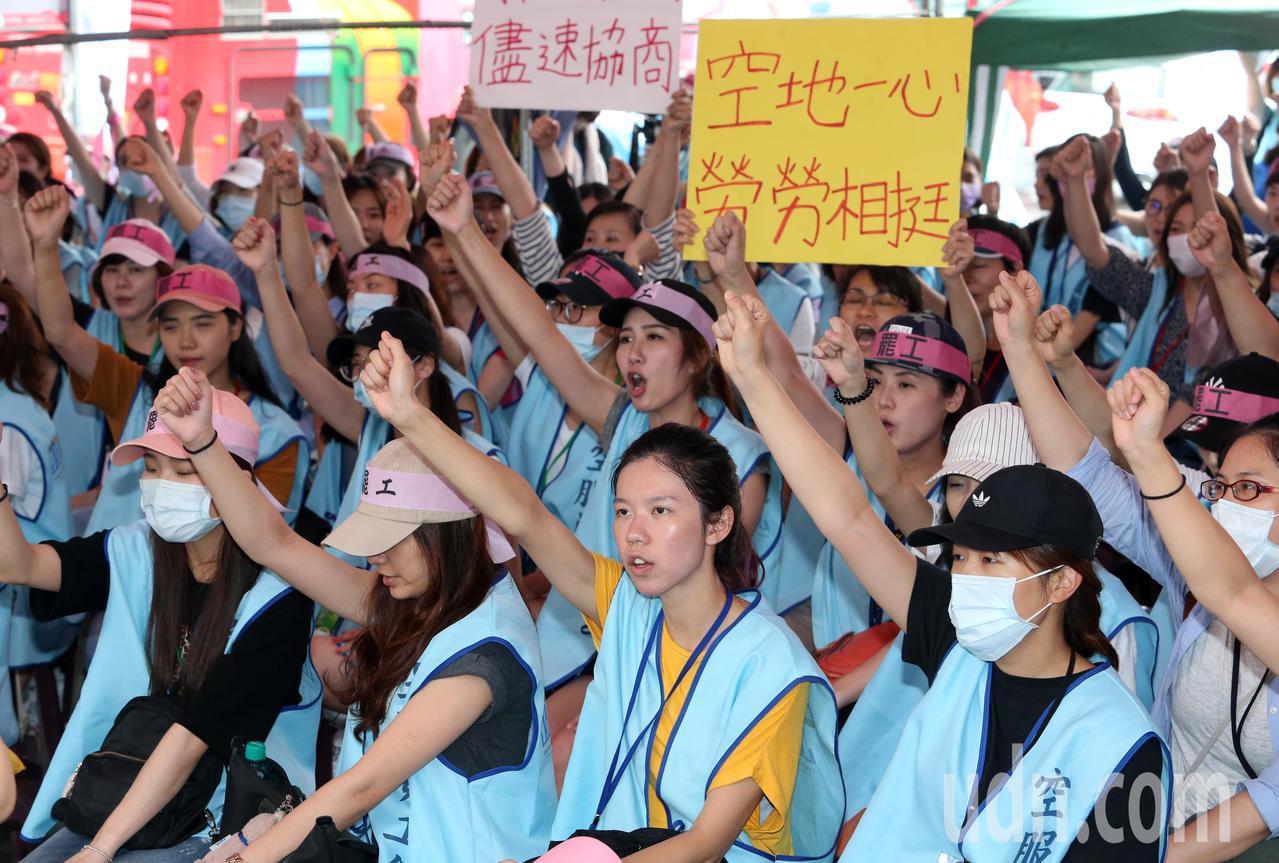 參加罷工的長榮空服員,拿著「空地一心,勞勞相挺」等標語,表達空服員與地勤都是勞工...