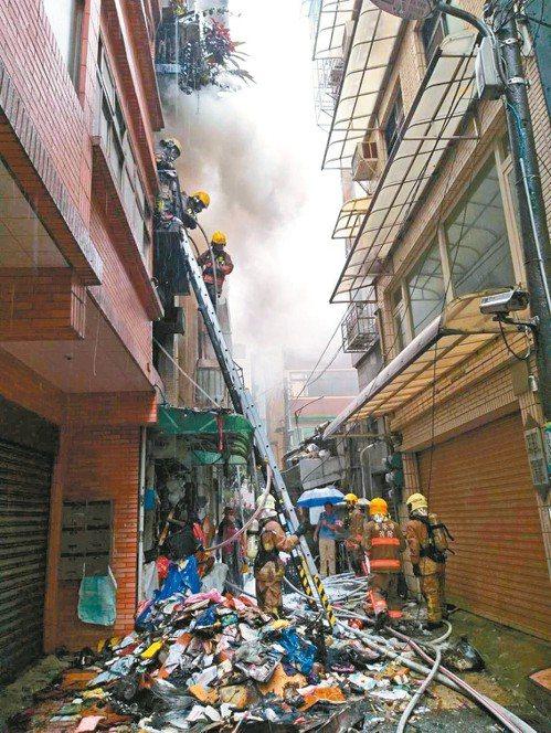 基隆市昨發生民宅火警,由於屋內堆滿回收物,消防人員一面滅火,一面清出雜物。 記者...