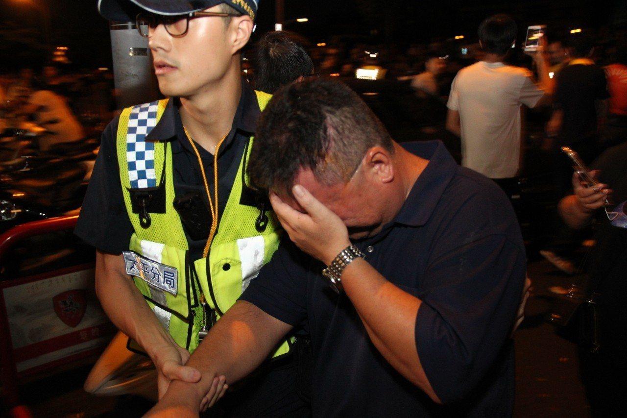 台中市太平警分局偵查隊長陳俊彥(右)在衝突中被辣椒水噴到臉,由警員扶到一旁休息。...