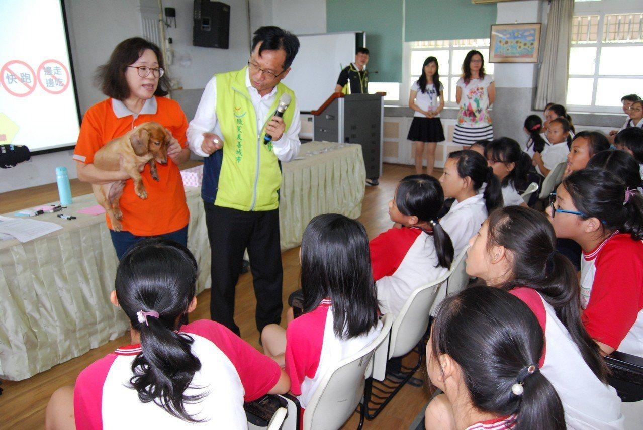 彰化市長林世賢今天到東芳國小宣導生命教育及如何面對流浪犬,他的妻子高德耘手中抱的...