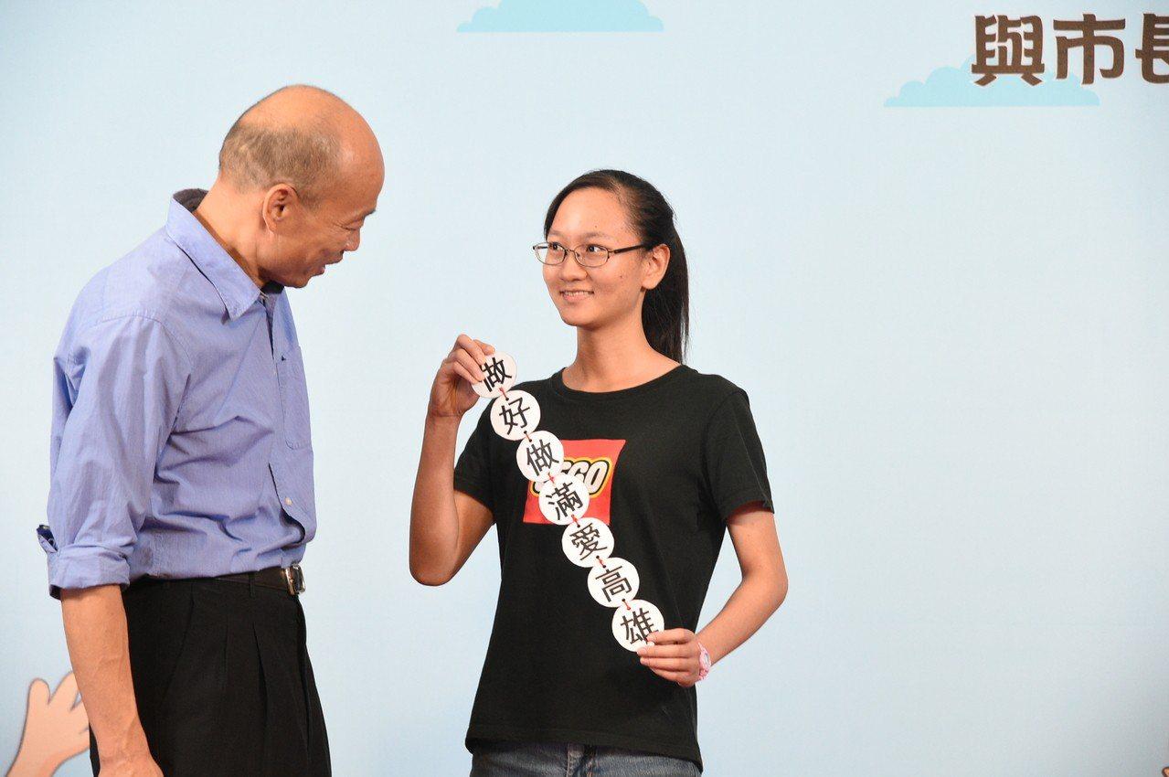 一名女學生與高雄市長韓國瑜合影時,突然秀出自製直型標語卡片「做好做滿愛高雄」。記...