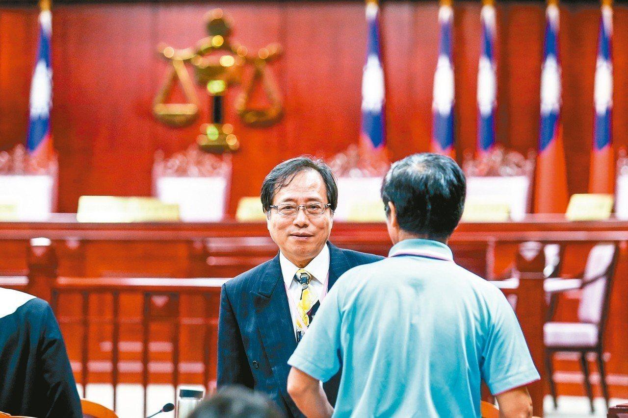 憲法法庭昨天召開公務員年改釋憲案言詞辯論,休息時間鑑定人李來希(左)跟與會人員交...