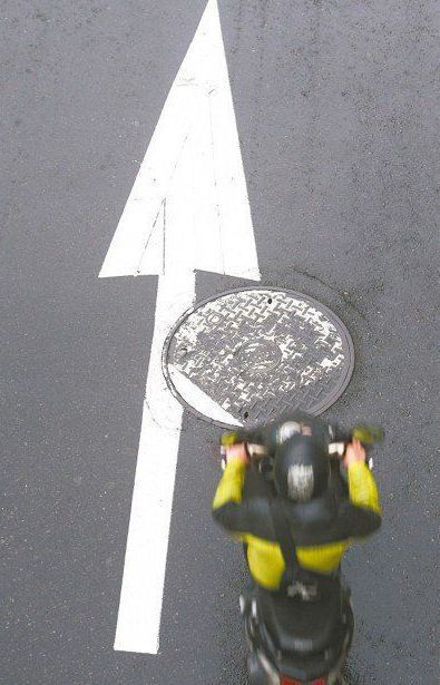 下雨天時,路上人孔蓋與標線常是騎士摔車的「隱形殺手」。 圖/聯合報系資料照片