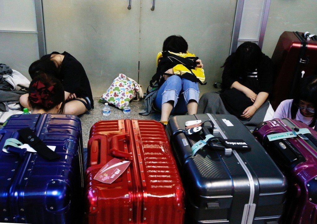 由於班機取消,學生只能坐在地上休息補眠。 圖/鄭超文