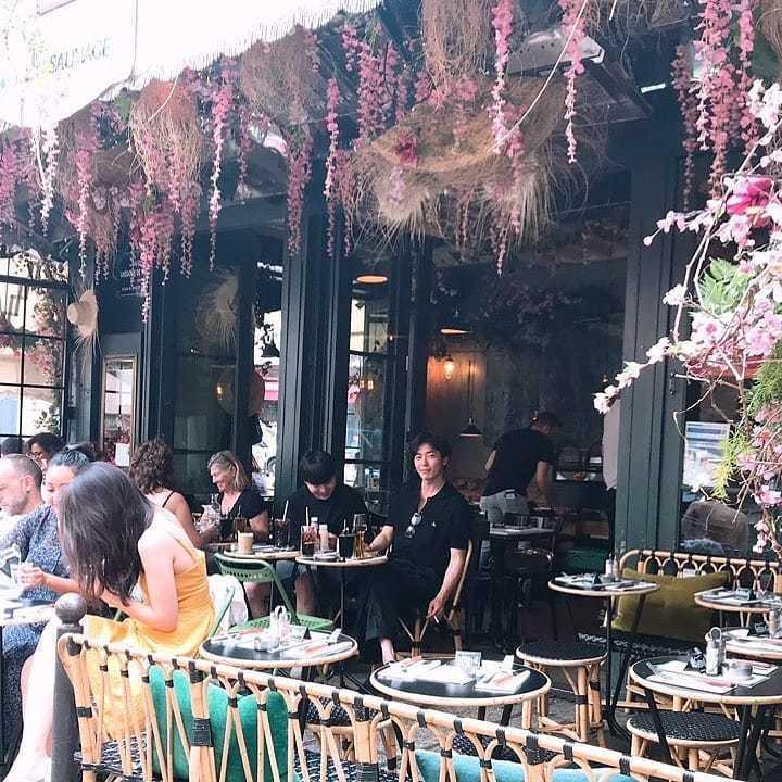 金材昱身穿Vivienne Westwood的Polo衫在咖啡座,手上夾著菸也不...