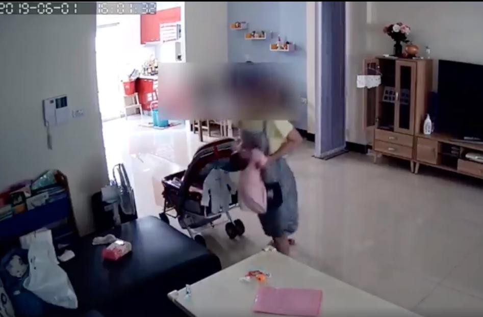 台南一名月嫂抱起新生兒直接拉住他的雙手,未扶頭部、脖子。圖/擷取youtube