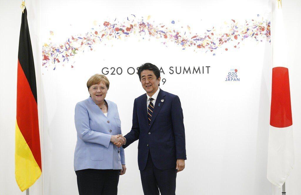梅克爾(左)如期抵日出席G20領袖峰會。 圖/美聯社