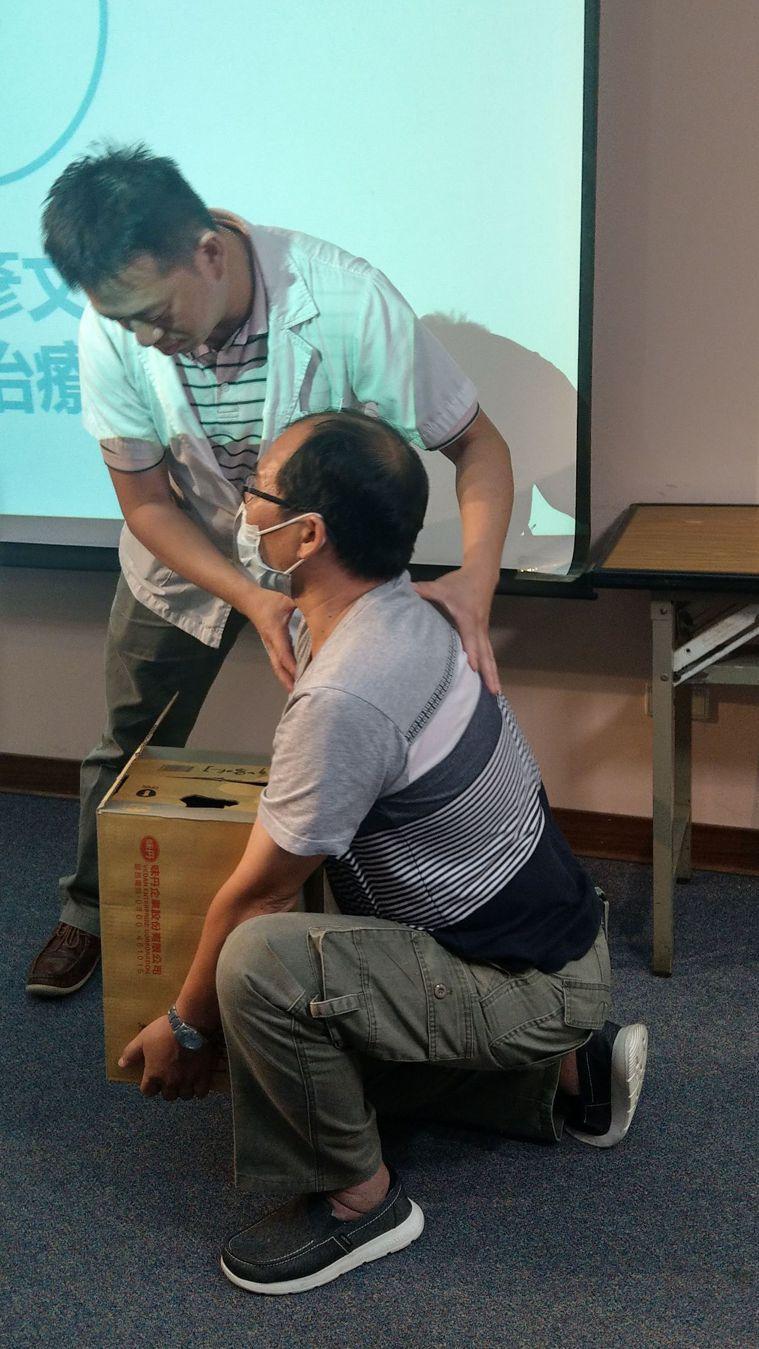 物理治療師陳彥文(後)指導紀姓居家照服員(前)蹲下搬重物,收下巴,腰背要挺直。記...