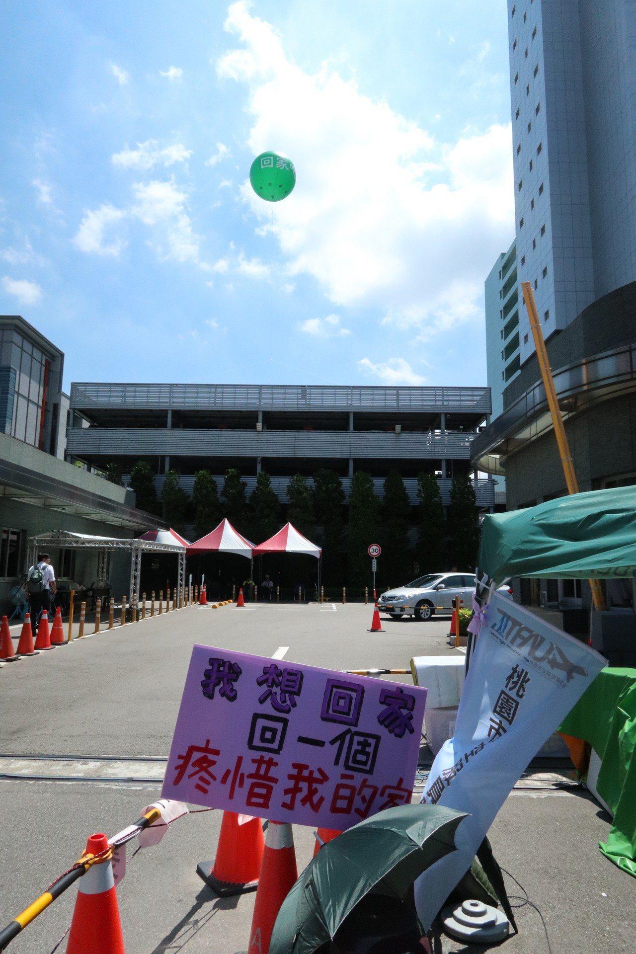 長榮罷工持續進行,資方昨日高掛「回家吧」氣球向空服員喊話,工會則製作「我想回家,...