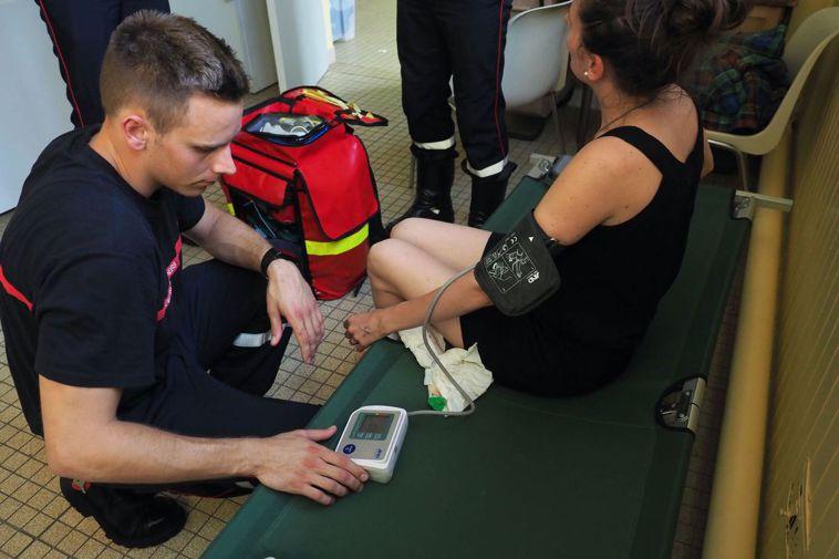 醫護人員幫婦女量血壓。 (法新社)