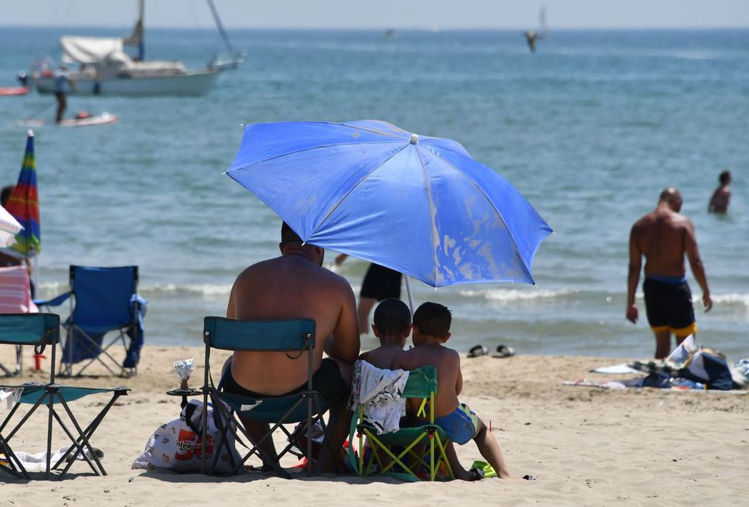 法國南部帕拉瓦萊弗洛特海灘的遊客躲在遮陽傘下。 (法新社)