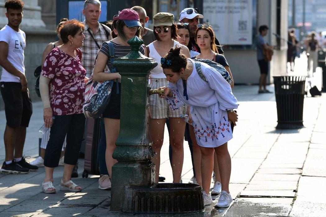 義大利連日高溫,米蘭主教座堂旁的飲水機28日有不少民眾排隊喝水。 (法新社)