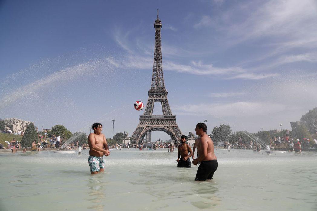 民眾在巴黎艾菲爾鐵塔附近的水池戲水。 (法新社)