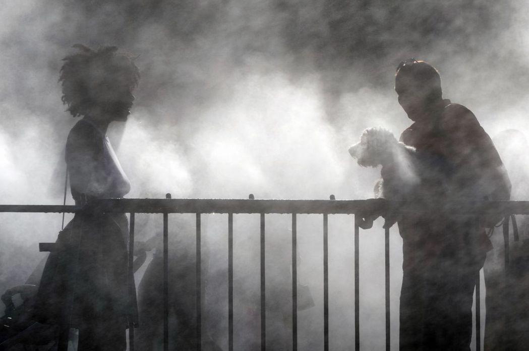 法國東部史特拉斯堡民眾在市中心廣場的噴霧器旁降溫。 (法新社)