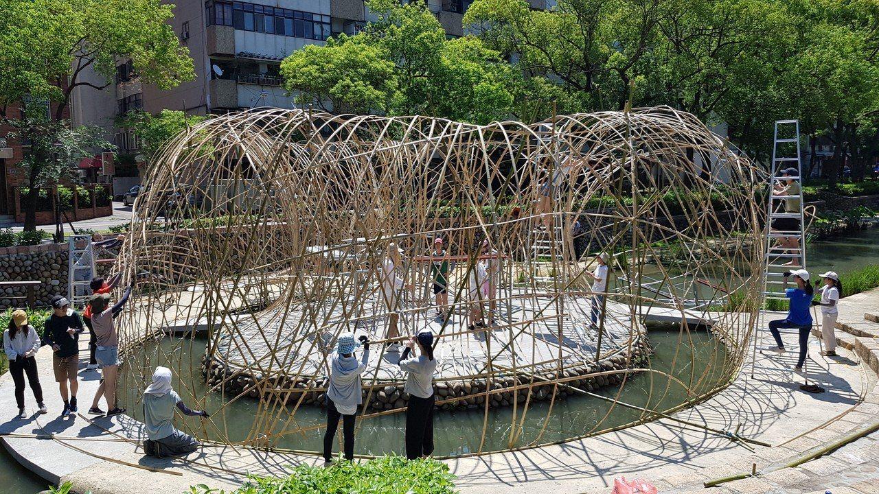 香港大學學生連日來冒著酷熱在護城河趕工編製竹構築TOROO。 記者黃瑞典/攝影