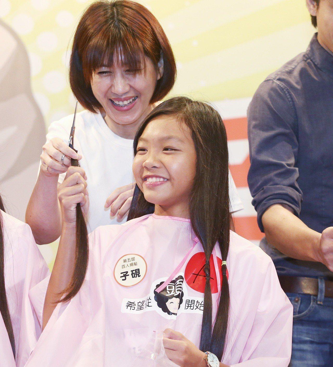 由癌症希望基金會舉辦的第五屆百人捐髮活動,共有124名捐髮者,徐子硯(右)是游泳...