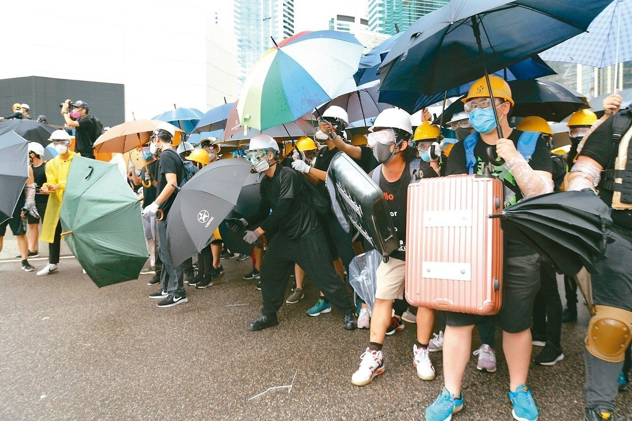 香港反送中抗爭持續,不少抗爭者拿著自製盾牌,戴著雨傘、防毒面具與口罩,與警方對峙...