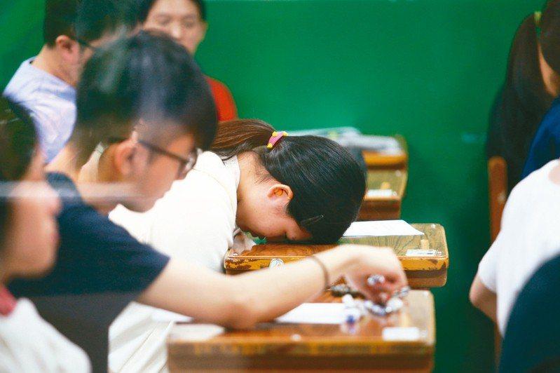 大學指考7月1日至3日舉行,上午第一天考物理、化學、生物,一位考生考完後在等待收考卷的空擋,趴在桌上沉思。 記者蘇健忠/攝影