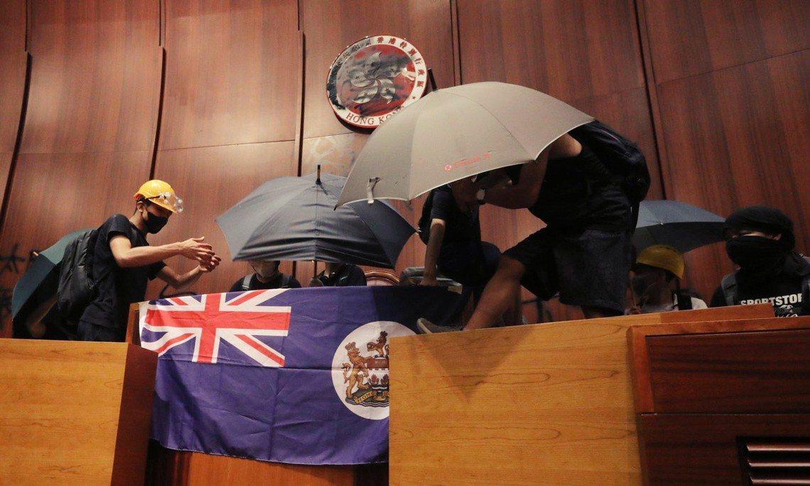 香港立法會議事廳內,示威者將特區政府的區徽噴漆塗黑,並在台上掛上「港英旗」。 圖...