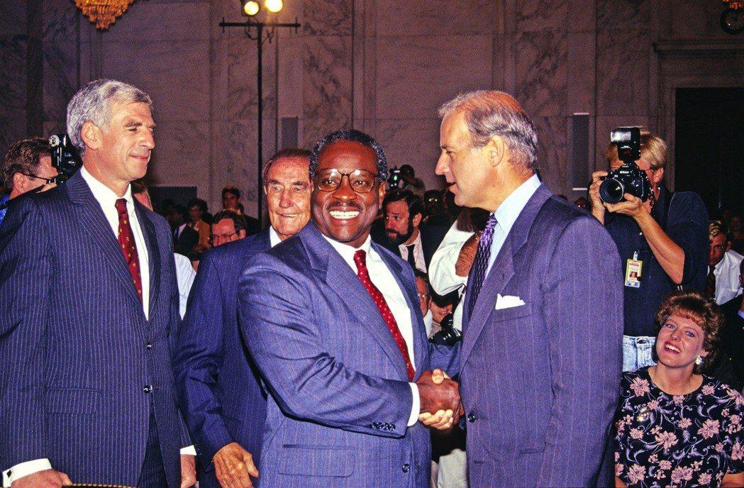 1991年,湯瑪斯(Clarence Thomas,圖中央與拜登握手者)被爆出性...
