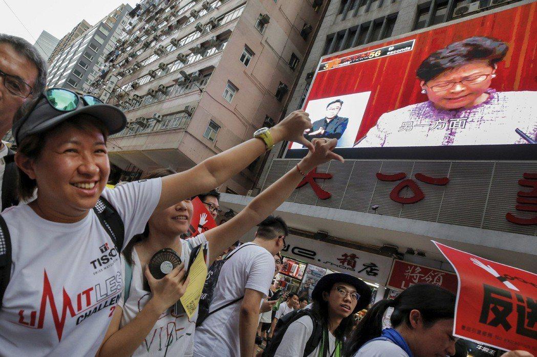 6月9日數百萬人上街遊行反送中,民眾對路旁的電視牆報以噓聲。 圖/美聯社