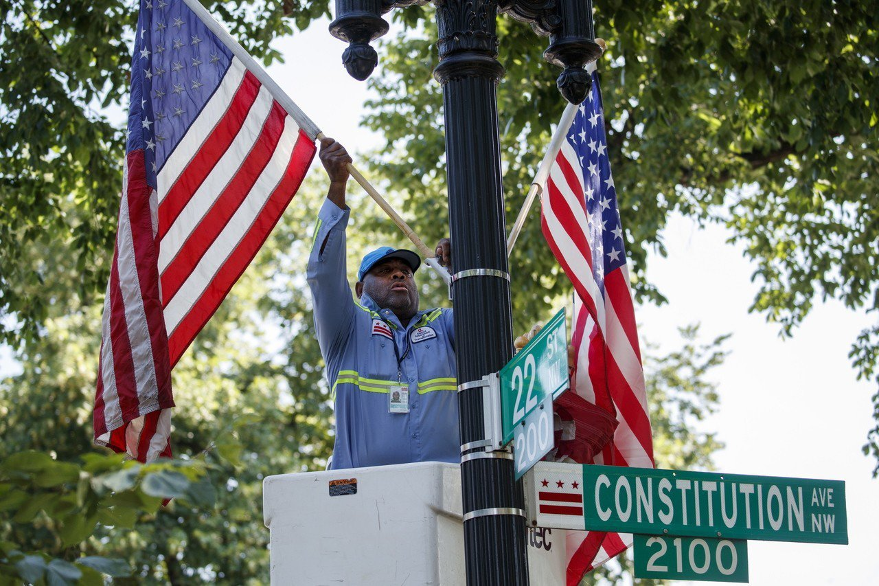 華府工作人員正在國家廣場大草坪四周插上國旗,迎接國慶日。 (歐新社)