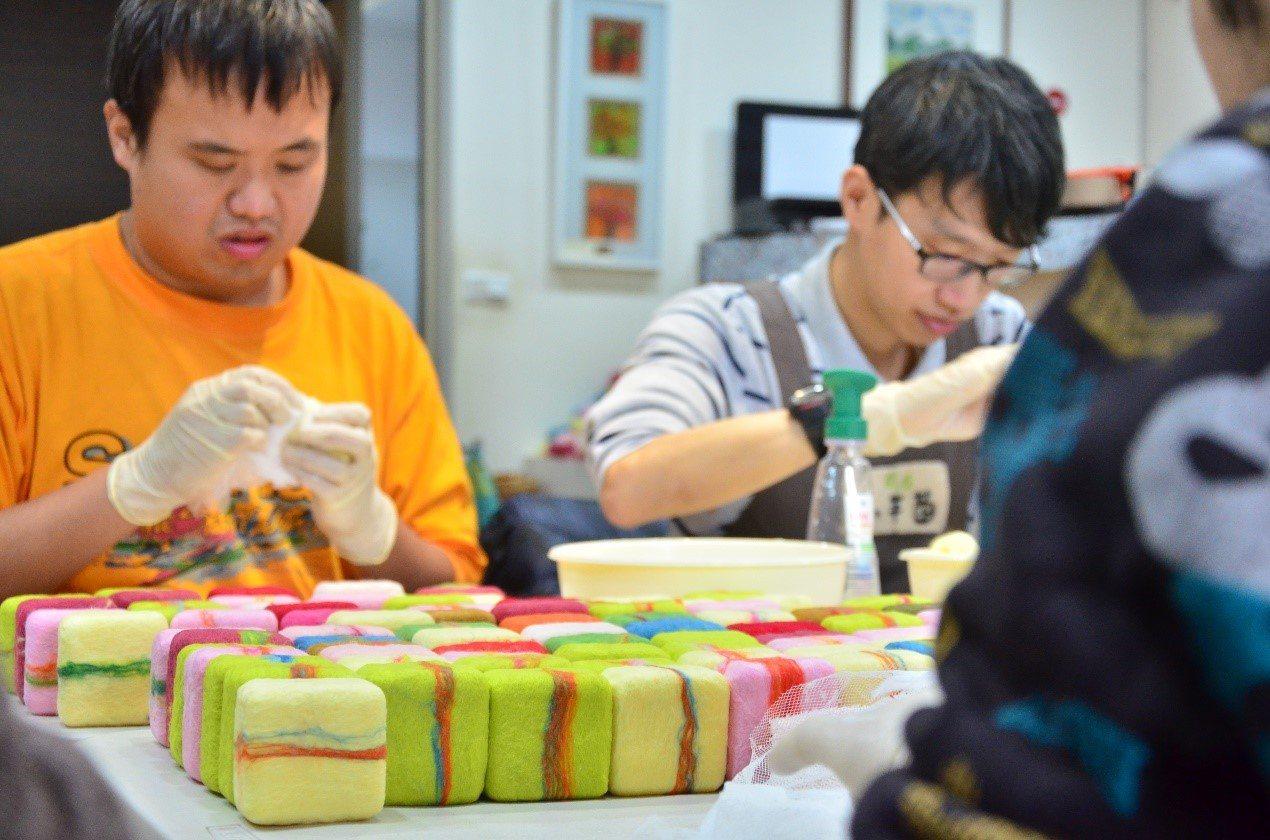 「小羊苗庇護工場」的羊毛皂獲得3家企業的青睞,庇護員工開心地趕工包裝。圖/新北勞...