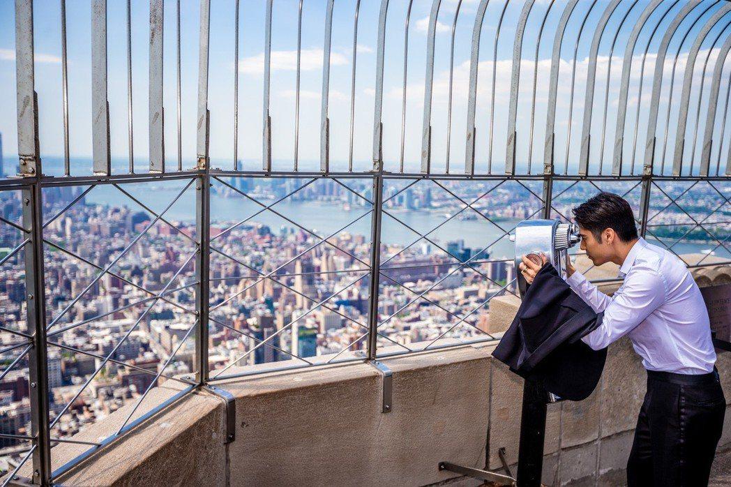 胡宇威透過望遠鏡仔細欣賞紐約市景。圖/寶麗來國際娛樂提供