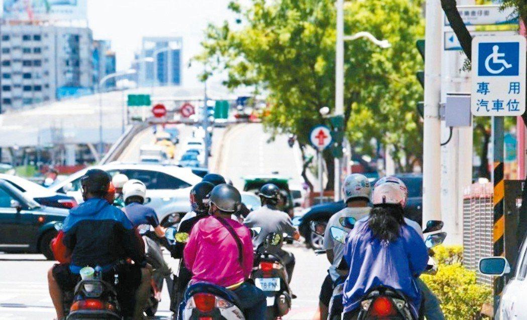 炎夏高溫讓人快受不了,停等紅燈的機車騎士聚集在樹蔭下躲太陽。 圖/聯合報系資料照...