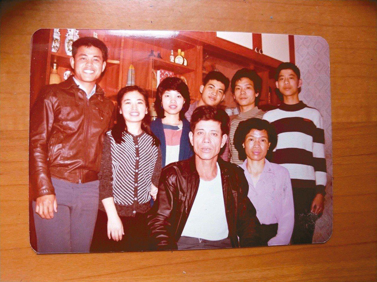 吳鈞堯(後右三)與家人合影。右上邊米白色櫃子,即為存放本文《弦民歌》的地方。