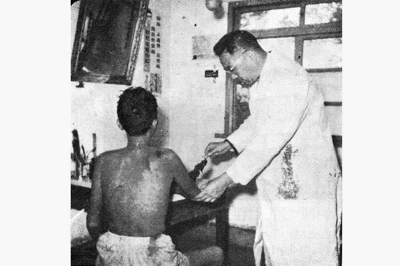 成立於1954年的樂生療養院門診部,醫生正拿雞毛輕觸患者的皮膚,測試是否喪失觸覺。 圖/作者提供;來源/《癩病防治十年》,1963年出版