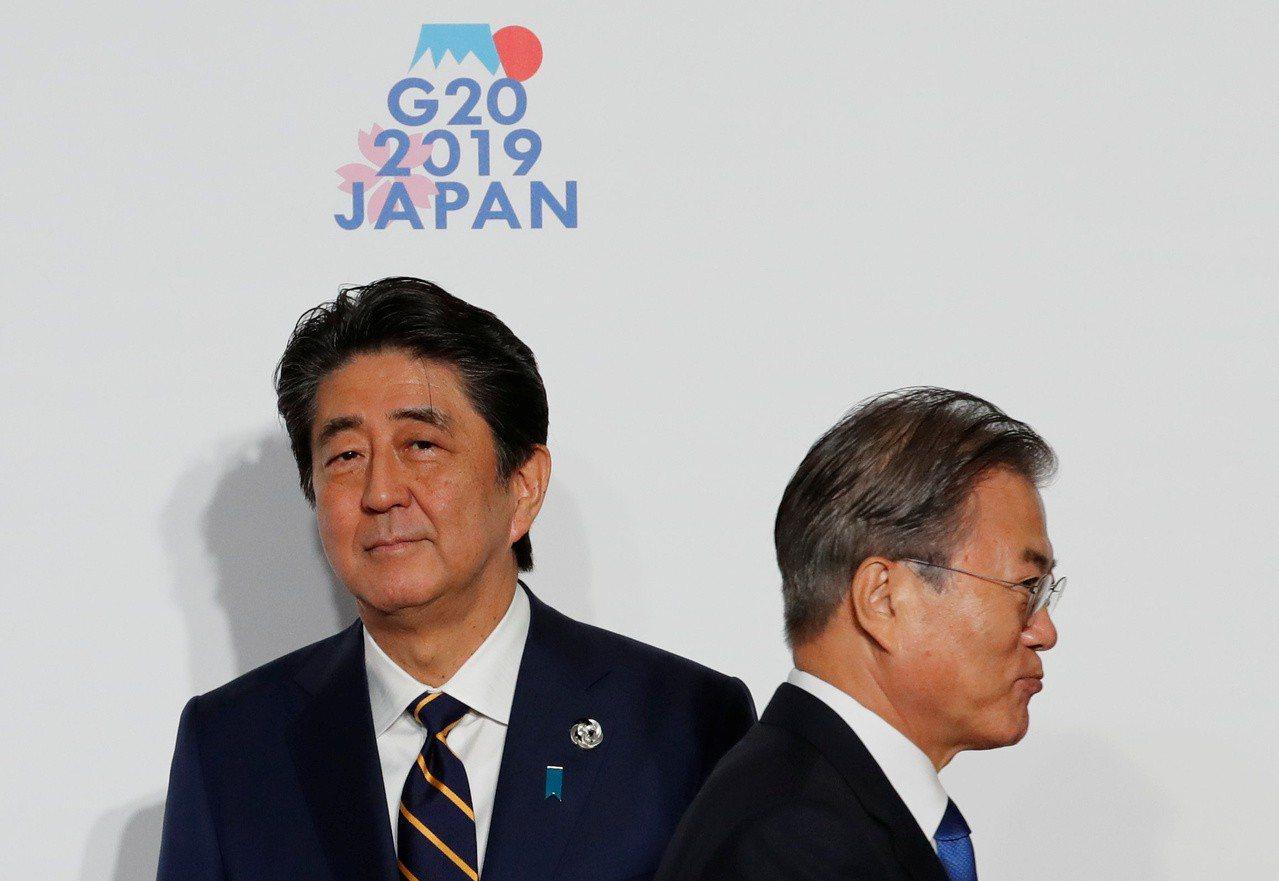 日本首相安倍晉三(左)與南韓總理文在寅在G20上互動冷淡,僅合照8秒鐘。 (路透...