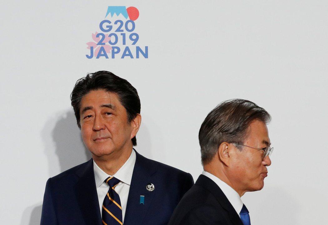 日本首相安倍晉三(左)與南韓總理文在寅在G20上互動冷淡,僅合照8秒鐘。 (路透)