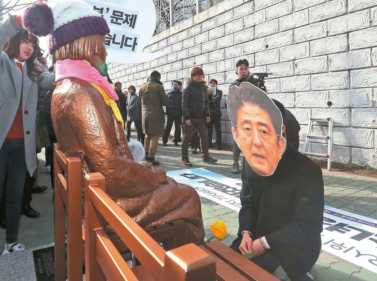 慰安婦問題影響日韓關係,圖為南韓抗議者戴上日本首相安倍晉三的面具,跪在少女雕像前...