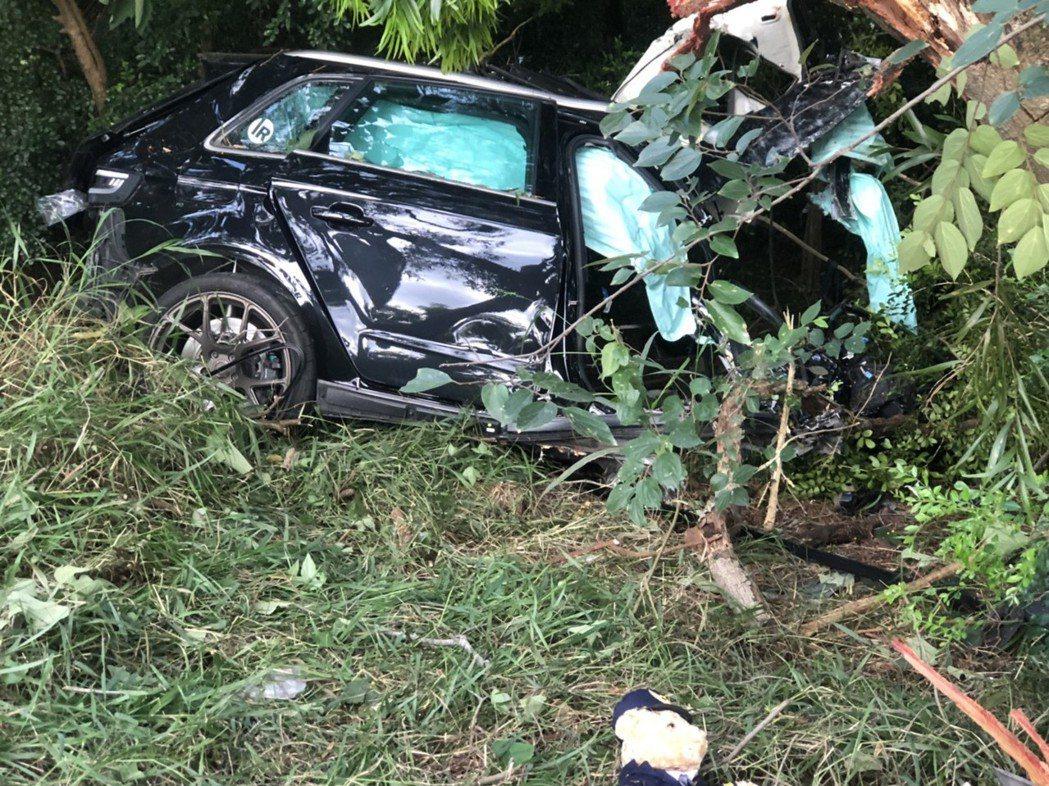 黑色轎車飛越護欄衝撞邊坡樹叢,車體折斷成兩截,駕駛慘死。記者林昭彰/翻攝