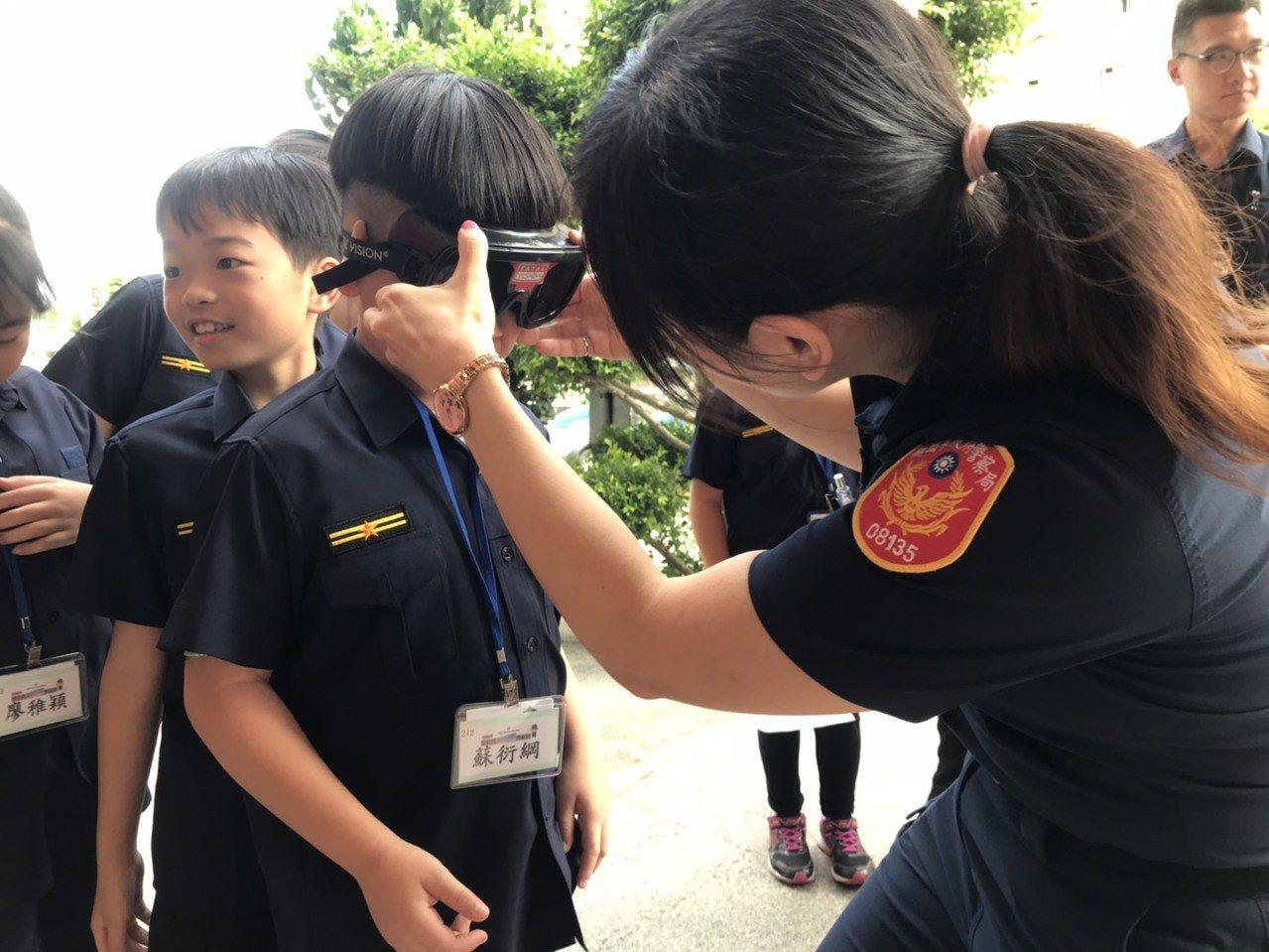 平鎮警分局暑假青春波麗士神探體驗營,為宣導勺酒駕,安排參與青少年試戴上酒後眼鏡,...