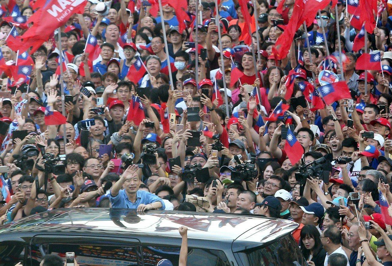 高雄市長韓國瑜(車子旁邊中間位置)今天到六合夜市快閃,被蜂湧的韓粉圍得寸步難行。...