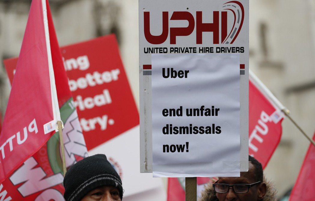 在倫敦皇家法院舉行勞工權益聽證會前,示威者和零工經濟工作者在門口抗議優步(Ube...
