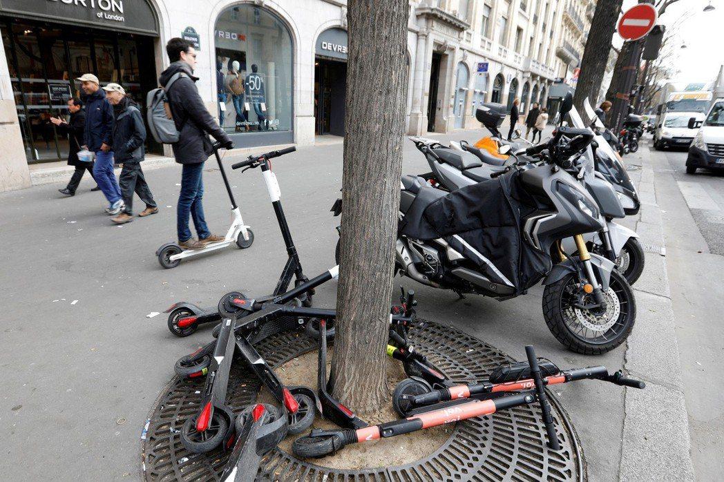 一名男子將電動滑板車騎上人行道。從本月開始,巴黎禁止在人行道騎滑板車。(路透)