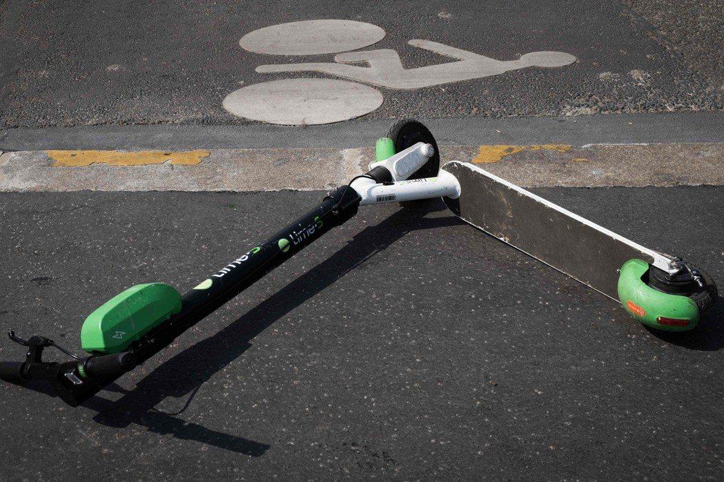 一輛電動滑板車被丟在巴黎的人行道。(法新社)