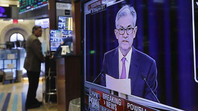 美國聯準會(Fed)主席鮑爾上月在決策會後召開記者會,紐約證交所交易員在一旁緊盯...