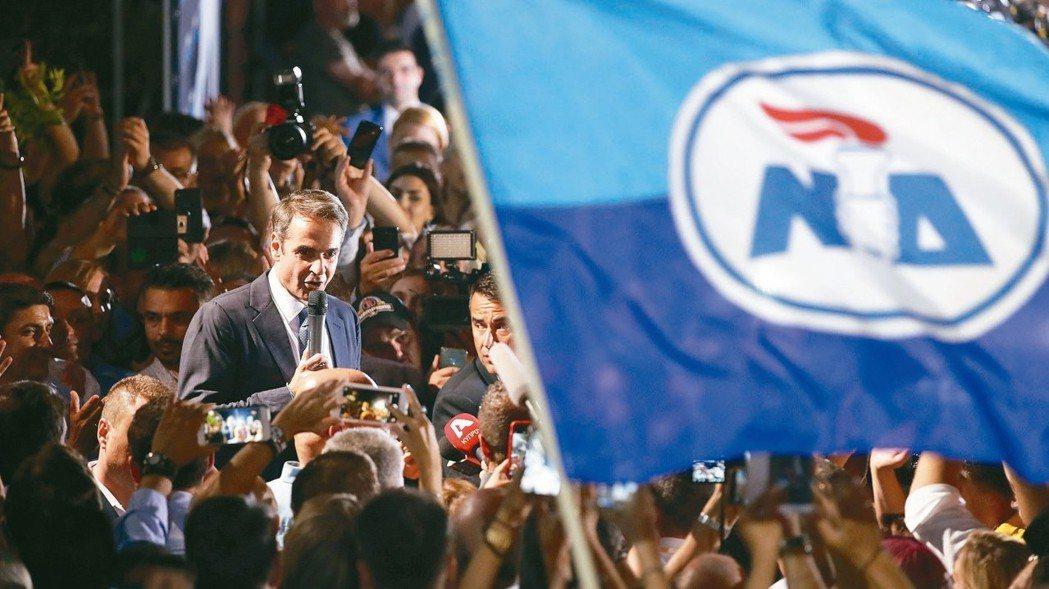 希臘新民主黨7日在國會大選贏得過半席次,黨魁米佐塔基斯(圖中焦點)與支持者慶祝勝...