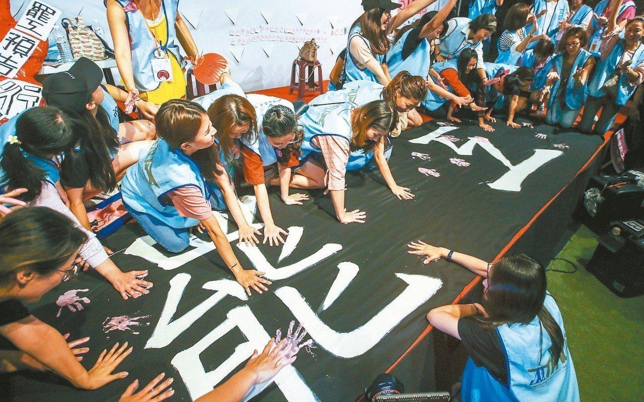 桃園市空服員工會從突襲罷工到落幕,空服員一一在罷工的黑布條上蓋上手印,慶祝成功。...