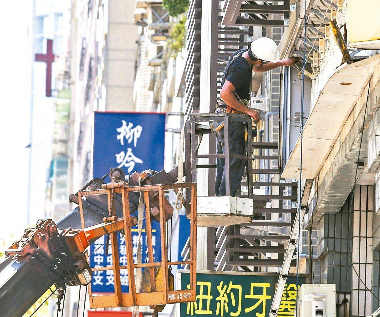 圖為一名工人在炎炎夏日下修理招牌。 圖/聯合報系資料照片