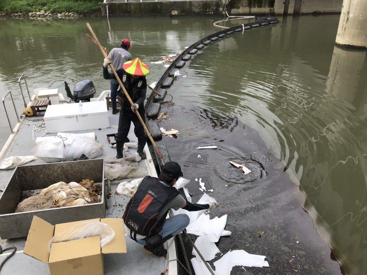 高雄市環保局人員以吸油棉清除愛河河面上的油汙。圖/高雄市環保局提供